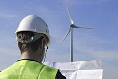 Technician in hard hat with paperwork in front of wind turbine.  (Renewable Energy).