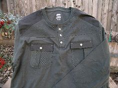 "This item is a new Route 66 brand shirt with its tags still attached. It is a long sleeve pull-over (Henley) with contrasting panels sewn into the shoulders, and also has additional detail like chest pockets with flaps, and re-enforced elbows. It is grey/green in color and has a total of five ""KF 7.62"" (308 Winchester) Brass Button Works buttons already sewn on it. This item is a size 'Large' and is ready to wear and go."