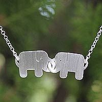Sterling silver pendant necklace, 'Elephant Friendship'  Locking their trunks, elephants become a symbol of true friendship in a necklace designed by Thailand's Jantana. The necklace is hand crafted of sterling silver, and the elephants received a brushed-satin finish.  .925 Sterling silver   NOVICA by National Geographic
