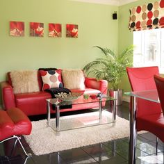GREEN & RED LIVING ROOM Bold red makes a statement against fresh green walls in this living room. Faux fur cushions and a textured rug keep the look cosy, while a glass coffee table creates a feeling of space, and its similarity to the dining table links the open-plan areas together.