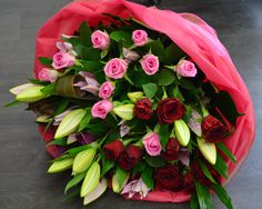 All about Love! Red Naomi roses , pink ...., pink oriental lilies, pink calla lilies, folded flax leaves, palm leaves and ballerina wrap