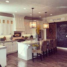 Love this white kitchen with lots of farmhouse flair including the rolling barn wood door, chalkboard wall and double lanterns over the large island kellyelko.com