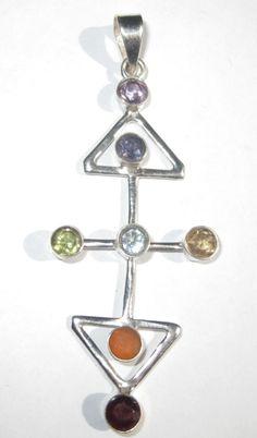 Très beau pendentif chakra en plaqué argent de forme allongée avec 2 triangles. Le pendentif chakra comprend 7 pierres gemmes facettées aux couleurs des chakras: améthyste, iolite, topaze bleu, péridot, citrine, cornaline et grenat