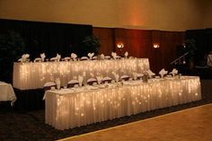 Uplighting is everything! Large bridal parties deserve gorgeous seating, and these theater style tables with white linens and soft gold lights help for a beautiful yet eye catching bit of table arrangement