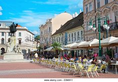 People at a street restaurant in the Old Town of Szeged. Lajos Kossuth sculpture in the left. - Stock Image