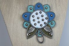 Color: Lt. Blue, Dk Blue and White with Brass Studs This lovely felt and zipper brooch is very well made. Brass zipper is added making for stunning embellishment along with some vintage bling The size is 3. in width and 3.5 in length. Perfect for the lapel of any jacket, coat or brim of