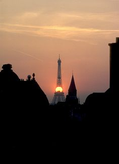 The setting sun behind the Eiffel Tower with silhouetted rooflines in  the foreground in Paris