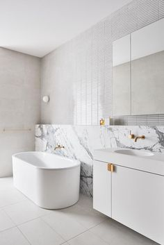 A heavily veined marble slab, mosaic wall tiles and brushed-brass accessories are a luxe touch in this white bathroom. Photo: Dan Hocking