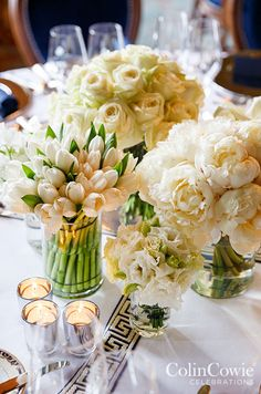 An elegant white table is adorned with monofloral arrangements of tulips, roses and peonies. Low Centerpieces, Wedding tabletop