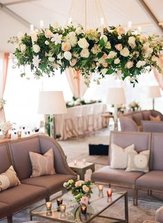 Chandeliers dripping in flowers hovered over gray upholstered furnishings at this Lowndes Grove wedding. | as featured in @charlestonweddings | photo: @lucycuneo | design: @calderclark | florals: @blossomsevents | venue: @pphgevents #lowndesgrove | #southernwedding #destinationwedding #luxurywedding