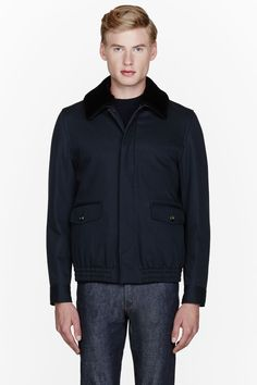 A.P.C. //  Dark navy shearling-collared jacket  32252M030003  Long sleeve jacket in dark navy blue. Spread collar with removable shearling trim. Button closure and flap pockets at front. Elasticized hem. Welt pockets at interior. Fully lined. Tonal stitching. Single-button barrel cuffs. Shell: 72% cotton, 28% polyamide. Lining: 100% viscose. Removable collar: sheep lined with 100% cotton. Padding: 100% polyester. Dry clean. Imported.  $805 CAD