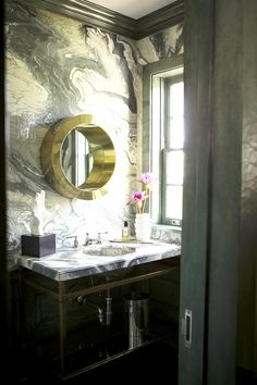 Marble walls in bathroom with brass mirror