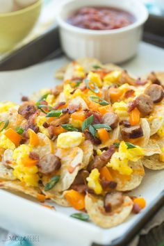 These Breakfast Nachos are topped with bacon, breakfast sausage, peppers, scrambled eggs and cheese and are perfect for your next brunch or even game day!