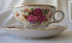 Vintage white 3 footed teacup and saucer set with pink and red roses and gold trim