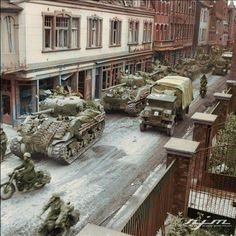 Sherman tanks of the British 8th Armoured Brigade (possibly 4th/7th Royal Dragoon Guards) and a Chevrolet truck leading ambulances through Amsterdamerstraße in Kevelaer North Rhine-Westphalia Germany 4 March 1945. Photo Colour by RJM