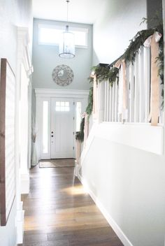 Soft Gray Walls Crisp White Woodwork And Champagne Toned Ribbons Keep This Entryway Merry