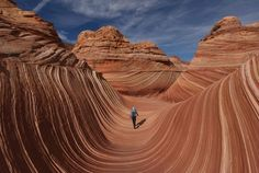 """Hikers walk amongst the unique U- shaped troughs of """"The Wave"""" rock formation at the Coyotes Buttes North wilderness area near Page, Arizona on October 30, 2017. The Wave is a sandstone rock formation in northern Arizona and was formed by a combination of water and wind erosion and due to its fragile nature, access is limited to only 20 hikers per day. (Photo by Mark Ralston/AFP Photo)"""
