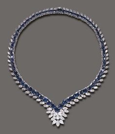 Blue Sapphire and Diamond Necklace of flexible V-shaped design, the graduated cushion-cut sapphire line, enhanced by marquise-cut diamond trim, the front accented by pear and marquise-cut diamond cluster detail, mounted in 18k white gold, 15¼ ins.