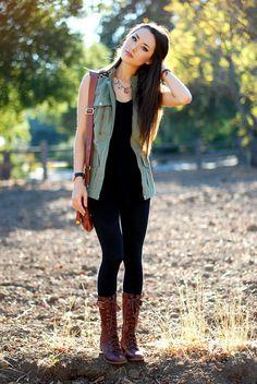 olive green sleeveless vest, black shirt, black leggings pants, brown combat boots