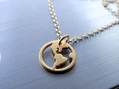This 24k globe charm.   19 Dainty Necklaces For Travel Lovers