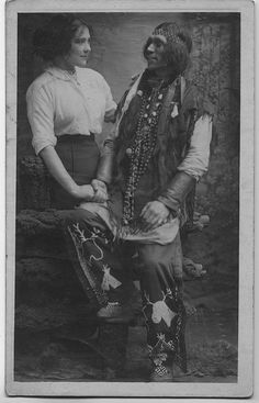 The looks these two are giving each other are quite interesting. Wish there was a story to go with the photo. Native american, indian, male, man, couple, white female, holding hands, friendship ? love even ? vintage, culture, photo b/w.