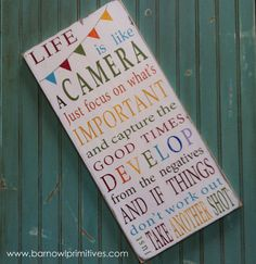 Life is like a camera. Just focus on whats important and capture the good times, develop from the negatives and if things dont work out, just take another shot.    I created this sign with a fun quote about capturing the good times in life and added a darling hand painted bunting to the top!    Completely hand painted on a quality pine board, this sign is distressed and antiqued for an aged, vintage finish. We make no attempt to cover natural wood markings, knots etc. as we feel this adds to…