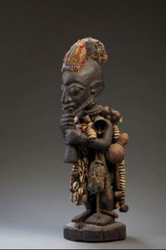 Africa | Esu from the Yoruba people of Nigeria | Wood, cloth, leather strips, cowrie shells, iron bell, beads, gourd | 20th century