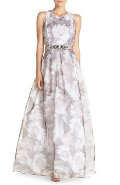 Faint, grey brushstrokes put a modern twist on this classic floral-print ballgown with an optional jeweled belt that draws in the voluminous silhouette.