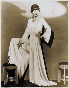 Anna May Wong, 1930s in dramatic white satin bias-cut jumpsuit with wide-legged trousers and flared sleeves-a twist on the classic white bias-cut satin gown of the 30s.