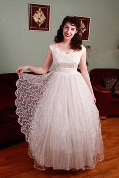 This vintage 1950s wedding gown has a classic shape with a graceful cut to the skirt and beautiful details. The bodice, covered in a pale ivory tambour lace of curving swirls, features a scalloped neckline and tiny caps of sleeves - just enough to curve over the shoulder. The basque waistline creates a flattering silhouette. The full length skirt offers no train, making the gown versatile for more casual weddings. It is lined with acetate, then has a full layer of tulle. The outer layer of…