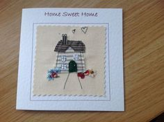 This house card was made with free motion applique where fabric shapes are sewn onto a canvas background. It would be very suitable for framing and keeping as a memento. Each card is individually handmade by me in my studio so small variations from the one in the photo make it uniquely special. By choosing and giving this unique handcrafted card, you are showing you care. The thick, good quality, (300gms) white card is lightly textured and measures 15cm square and comes with a white…
