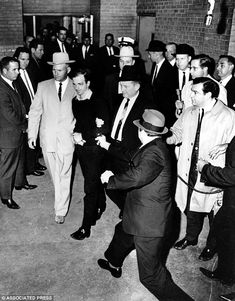 The accused assassin of President John F. Kennedy, Lee Harvey Oswald, center in handcuffs, is escorted to the Dallas city jail as nightclub owner Jack Ruby, foreground, approaches Oswald with a pointed revolver