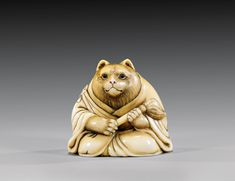 Aantique carved ivory netsuke depicting Tanuki with his whisk, Japan