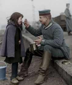 GERMAN SOLDIER SHARES A MEAL WITH BELGIUM CHILD