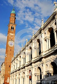 Photo taken at the Palladian Basilica in Vicenza in Veneto (Italy). In the picture you see the facade that looks north sunlit of great historic and beautiful building in the city center. In addition to the white church we see the slender bell tower with clock that penetrates into the blue sky speckled with white clouds.