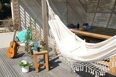 Décoration extérieur pour cet été, le hamac style folk en coton. Sur un terrasse avec fauteuil en rotin, guitare, tabouret en bois, pour passer de belles journées d'été.