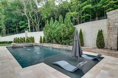 Modern style pool in spacious backyard features a tanning ledge with modern gray pool loungers. #modernpoolarea