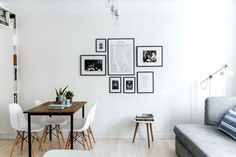 Modern dining space in white room with gallery wall and cacti on table