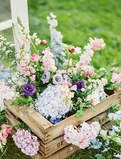 A rustic crate is the perfect container for a wild arrangement of pretty pastel flowers, including hydrangeas, lisianthus, snapdragons, and more.