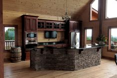 Hello dream kitchen! This Timber Block home is a custom built home, based on the homeowners dreams and ideas! We love everything about this, including the choice of the flat log profile, with the darker stained cabinets. We adore the granite countertops, with brick island! It's pure heaven! www.timberblock.com