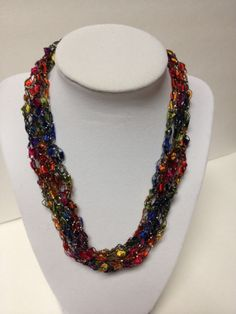 "Check my blog: http://centraltexascrafter.com/handcrafted-necklaces/ or direct link below.  Want the look of beads but enjoy the light-weight feel of yarn? Handcrafted, glittery and expandable bright, multi-colored necklace. Length can be adjusted from 18"" to 24"" with ease. No metal, no clasps - easy to put on and wear. You'll get so many comments on your ""beads"" - this unique necklace will garner you many compliments!"