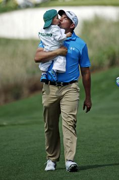 Scott Stallings kisses his son Finn during the par three competition at the Masters golf tournament Wednesday, April 9, 2014, in Augusta, Ga. (AP Photo/Matt Slocum)