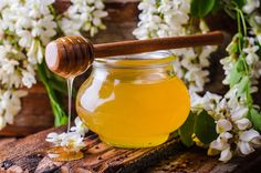 Pic: Acacia honey in gar on wooden background. Spring mood. Selective focus. Toned image