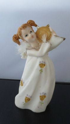 She is beautiful. Blond pigtails and white feather wings. No chips or cracks. In excellent condition.