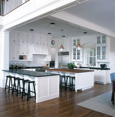 An all-white open kitchen with butcher-block-topped island  : Connecticut Cottages & Gardens
