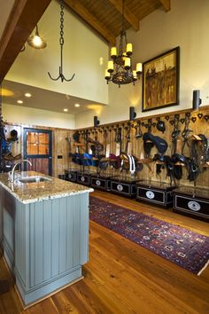 I think I can do without a chandelier, but everything else is just my style! Simply organized saddles, bridles, and trunks with a station for tack and hand washing.