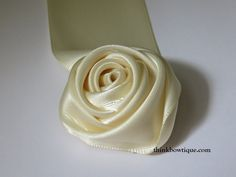 Silk Ribbon Embroidery Flowers Make a satin ribbon rolled rosette - Make a satin ribbon rolled rosette Fabric Roses Diy, Diy Lace Ribbon Flowers, Making Fabric Flowers, Ribbon Flower Tutorial, Ribbon Embroidery Tutorial, Ribbon Rosettes, Satin Ribbon Flowers, Silk Ribbon Embroidery, Flower Making