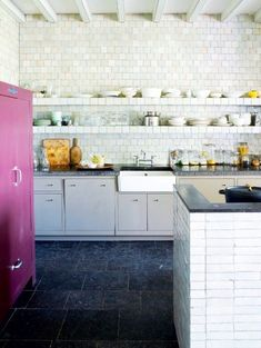 Zellige tiles used as a backsplash in a French kitchen with dark marble counters, floating sheleves and white cabinets