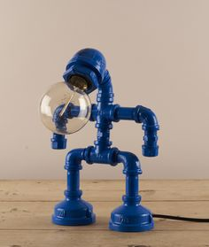 Blue Robot Lamp : This lamp is a truly unique piece of contemporary design. A robot fashioned from industrial pipe components, painted in bright blue and topped off with an industrial style filament globe bulb.