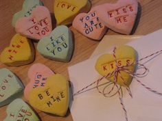 These are bakers clay - and they used a heart shaped cookie cutter and tiny alphabet stamps to imprint the message and then used fine tipped markers to fill in the color after baked.  great idea from the write start blog.